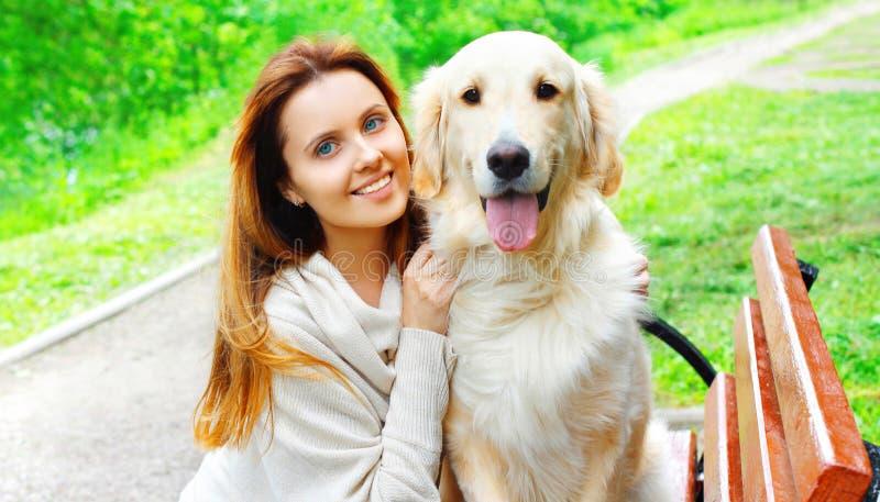 拥抱金毛猎犬狗的画象愉快的所有者妇女在城市公园 库存照片