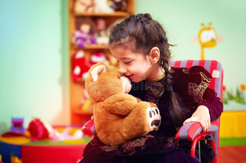 拥抱长毛绒熊的轮椅的逗人喜爱的小女孩在孩子的幼儿园与特别需要 免版税图库摄影