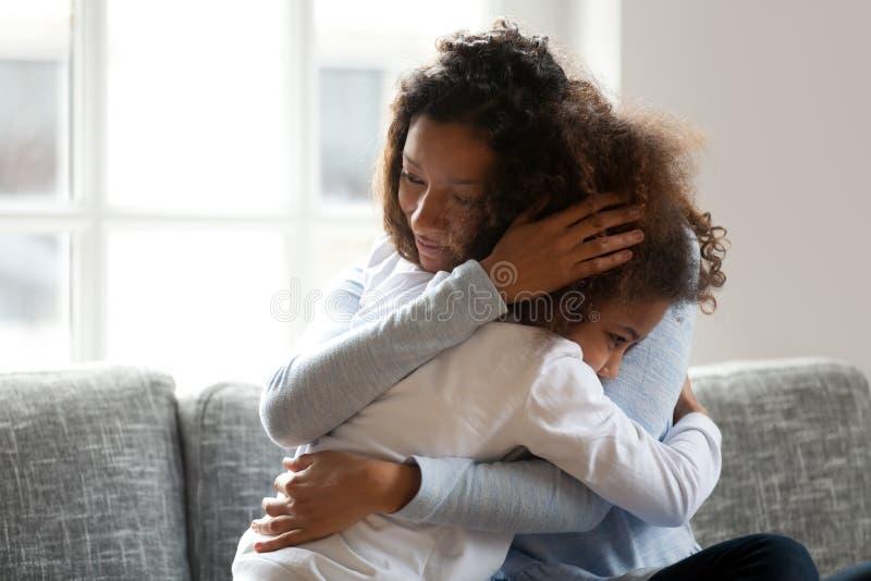 拥抱非洲女儿爱抚的古芝的爱恋的唯一黑人母亲 免版税图库摄影