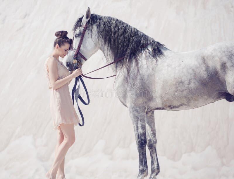 拥抱马的美丽的少妇 免版税库存照片