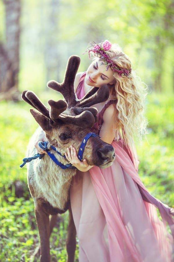 拥抱驯鹿的美丽的女孩画象 库存照片