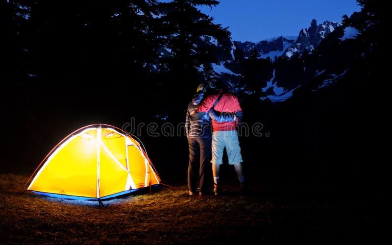 拥抱年轻人的夫妇 野营在山的夜 免版税库存图片