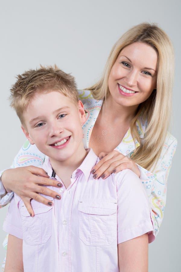 拥抱年轻儿子的愉快的微笑的母亲 图库摄影