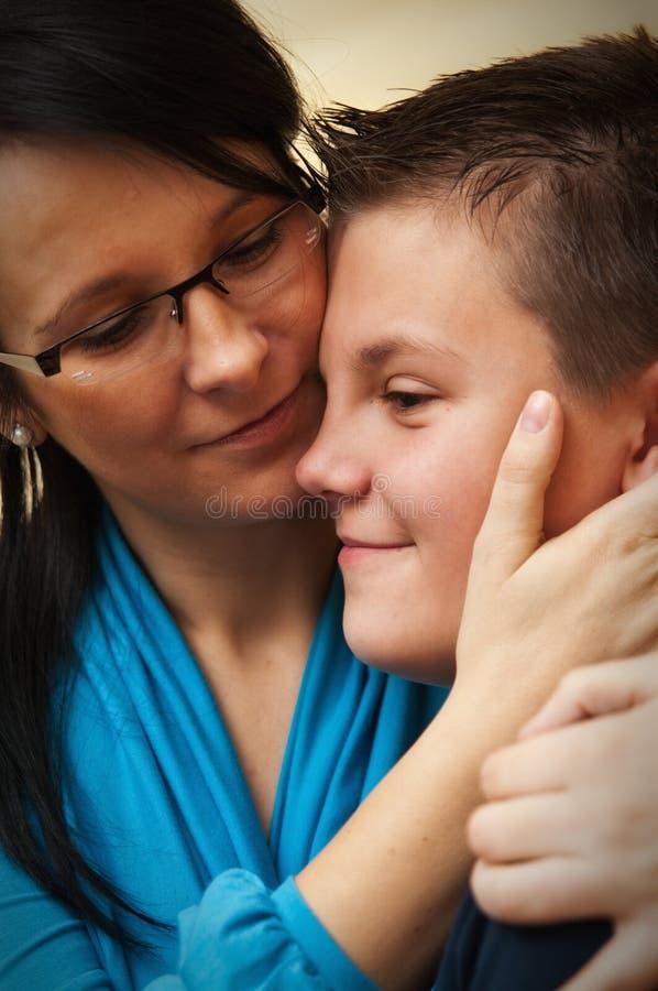 拥抱年轻儿子的母亲 免版税库存图片