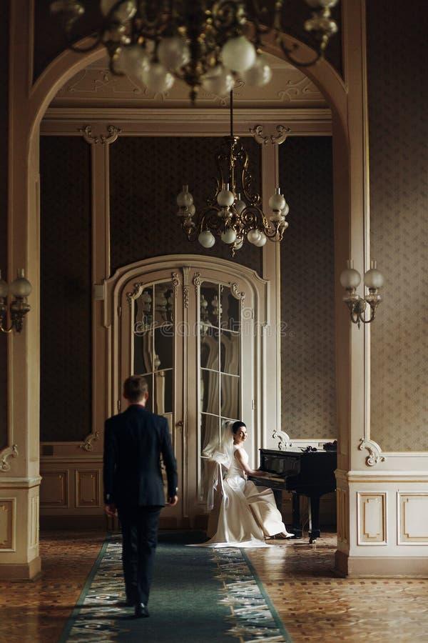 拥抱他华美的新娘的典雅的时髦的英俊的新郎,当时 免版税库存照片