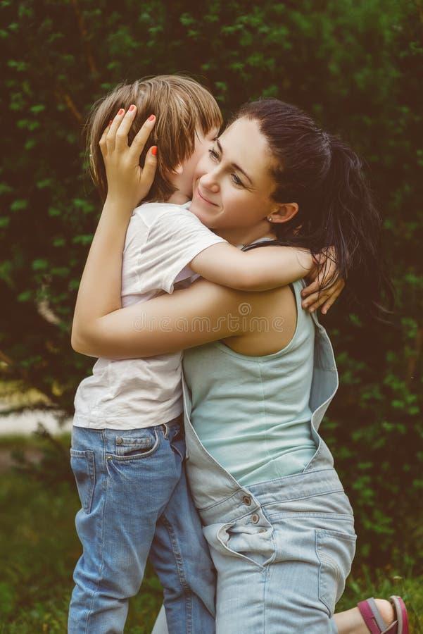 拥抱他愉快的母亲的爱恋的儿子在公园 温暖 库存图片
