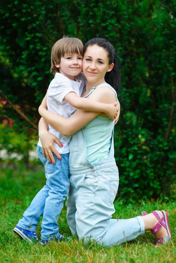 拥抱他愉快的母亲的爱恋的儿子在公园 免版税库存照片