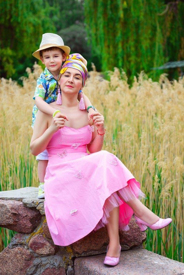 拥抱他时髦的母亲的爱恋的儿子在公园 库存图片