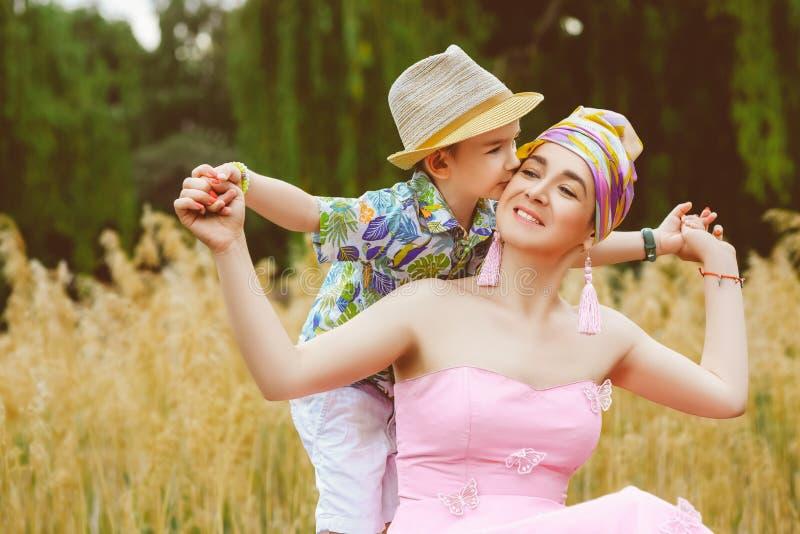 拥抱他时髦的母亲的爱恋的儿子在公园 免版税库存图片
