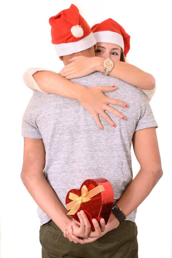 拥抱年轻的夫妇和圣诞节礼物 免版税图库摄影