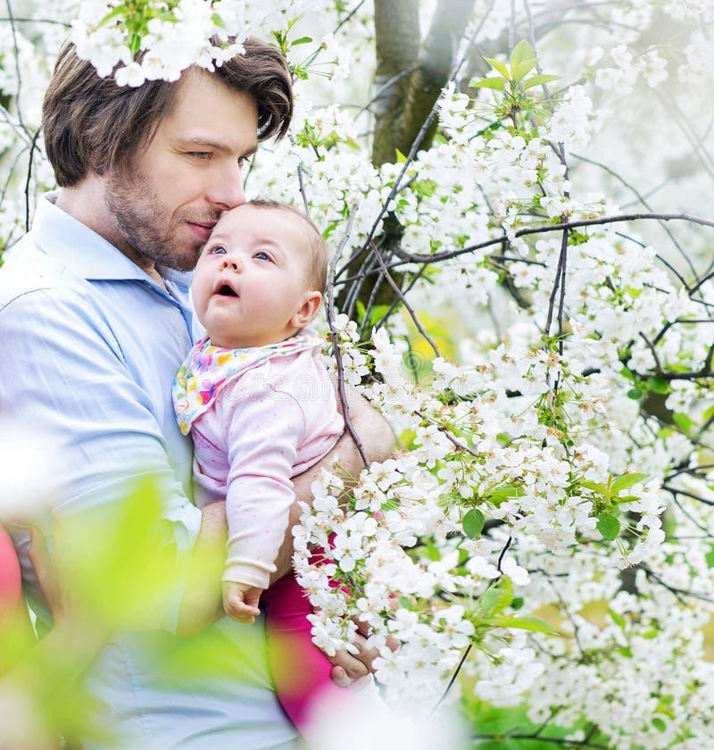 拥抱他的女儿的一个年轻父亲的画象 免版税库存图片
