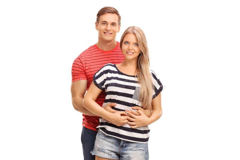 拥抱他的女朋友的年轻人 库存照片