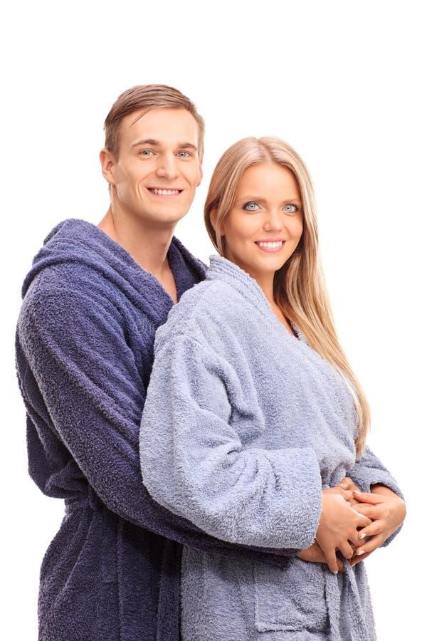 拥抱他的女朋友的浴巾的年轻人 免版税库存图片