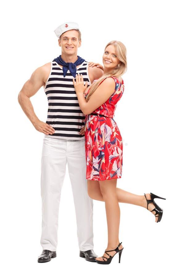 拥抱他的女朋友的年轻水手 库存图片