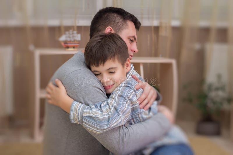 拥抱他的爸爸的哀伤的儿子室内 库存照片