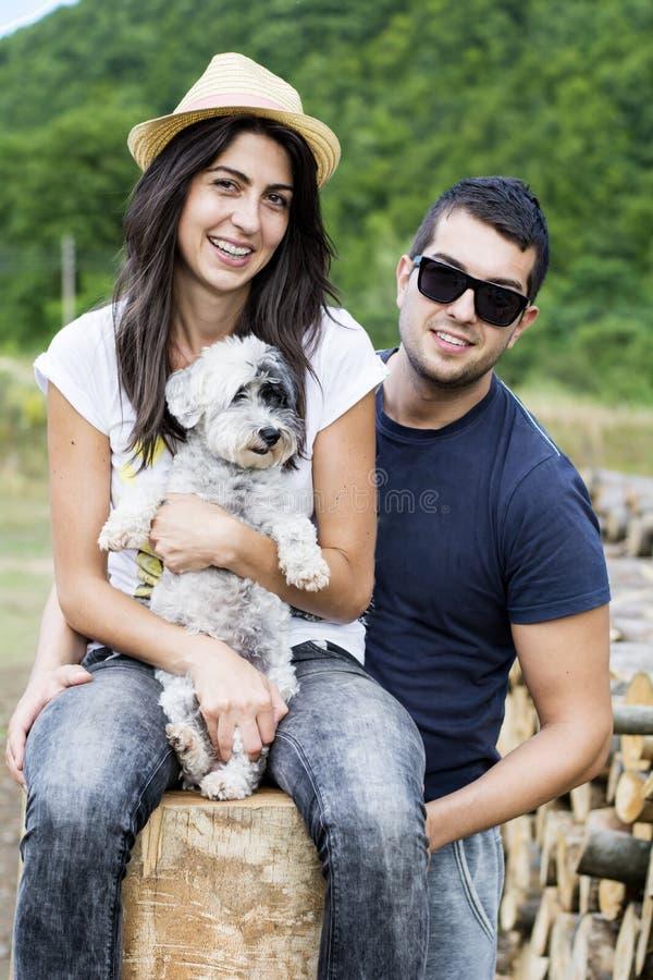 拥抱他们的白色狗的美好的微笑的夫妇室外 免版税库存照片