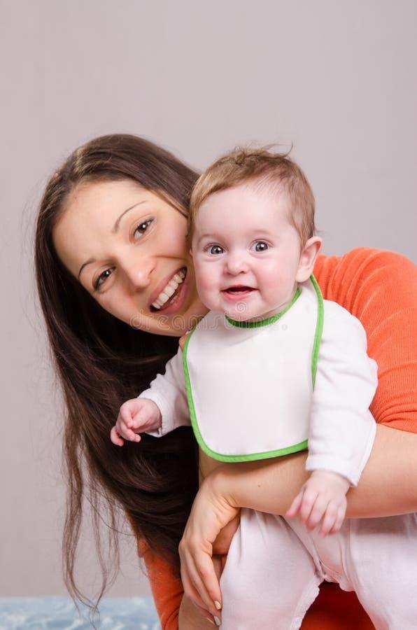拥抱围嘴的年轻愉快的母亲女婴 免版税库存图片