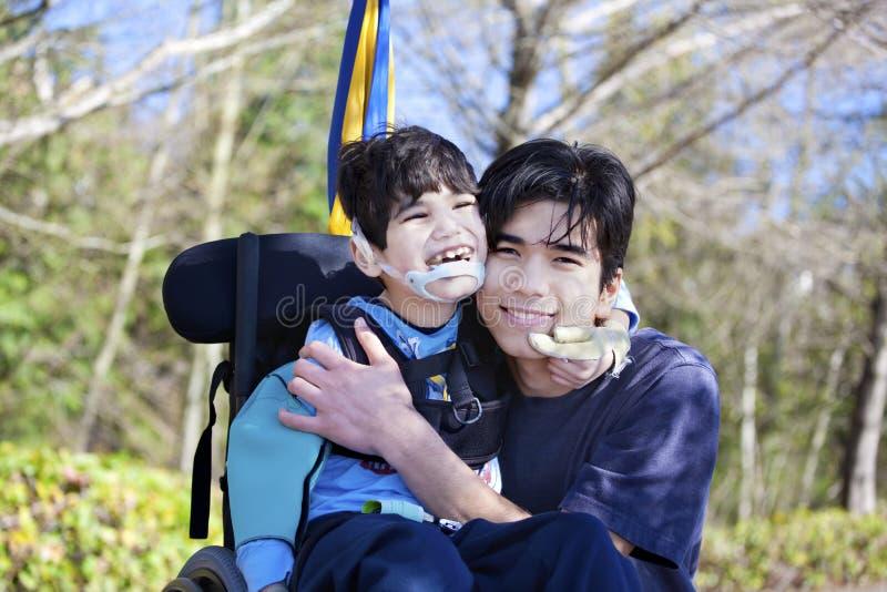 拥抱更老的兄弟的轮椅的小残疾男孩户外 免版税库存照片