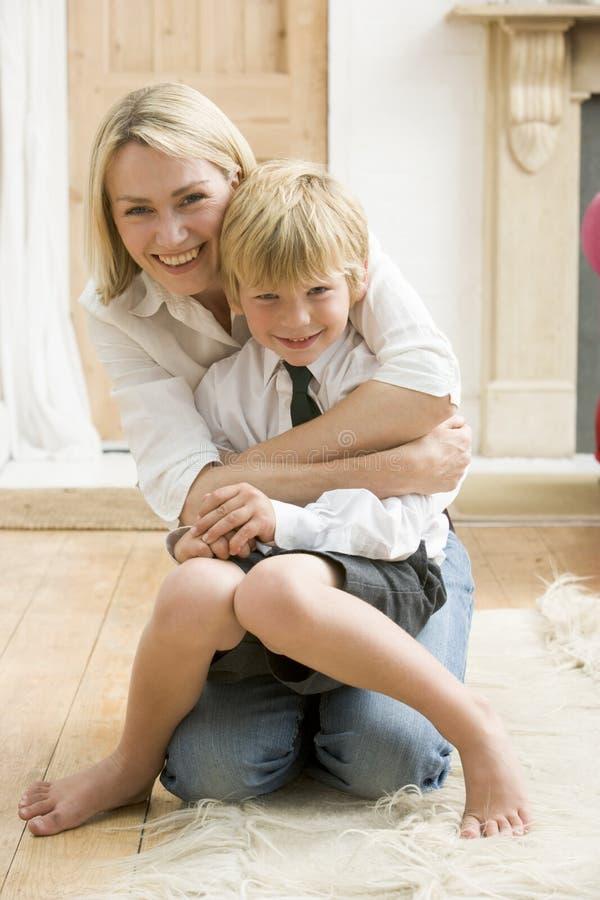 拥抱smili妇女年轻人的男孩前走廊 库存图片