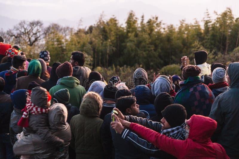 拥挤人民等待在新年与树的` s天黎明的黎明在背景中在老虎小山,大吉岭 库存照片