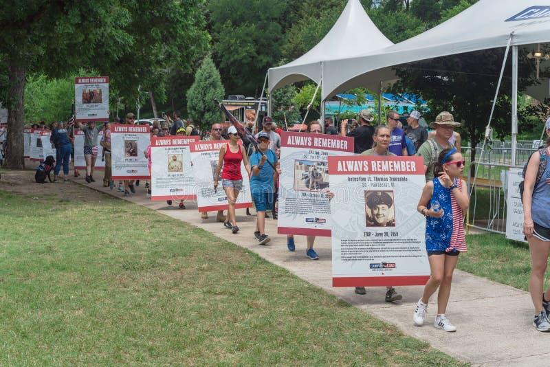 拥挤人民运载堕落的英雄照片招贴在阵亡将士纪念日游行 免版税库存图片