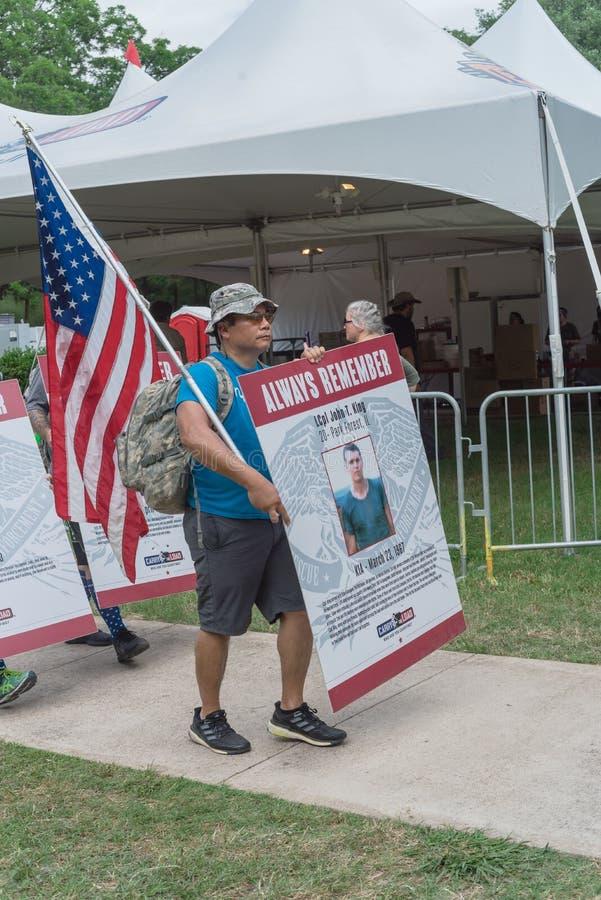 拥挤人民运载堕落的英雄照片招贴在阵亡将士纪念日游行 免版税库存照片