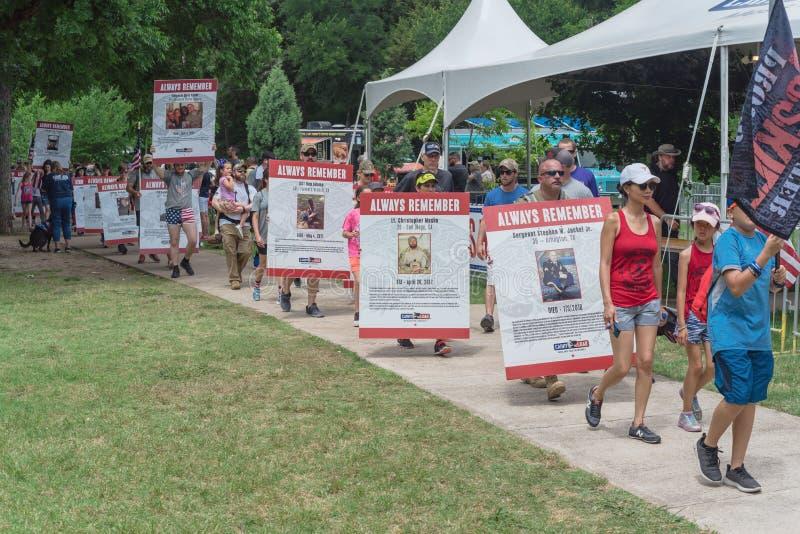 拥挤人民运载堕落的英雄照片招贴在阵亡将士纪念日游行 库存图片
