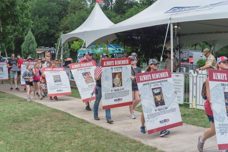 拥挤人民运载堕落的英雄照片招贴在阵亡将士纪念日游行 图库摄影