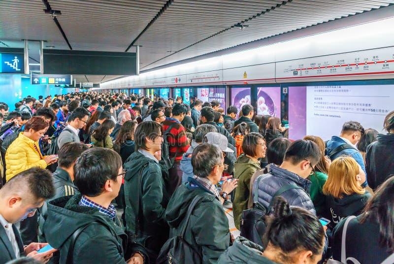 拥挤在地铁站的许多繁忙的中国人民在等待火车的香港中部区到达 免版税库存图片
