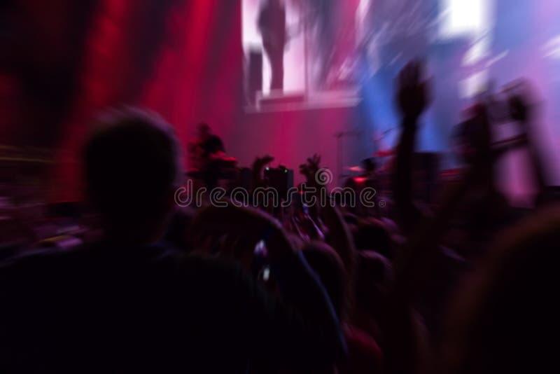 拥挤在音乐会在阶段下紫色光  免版税库存照片