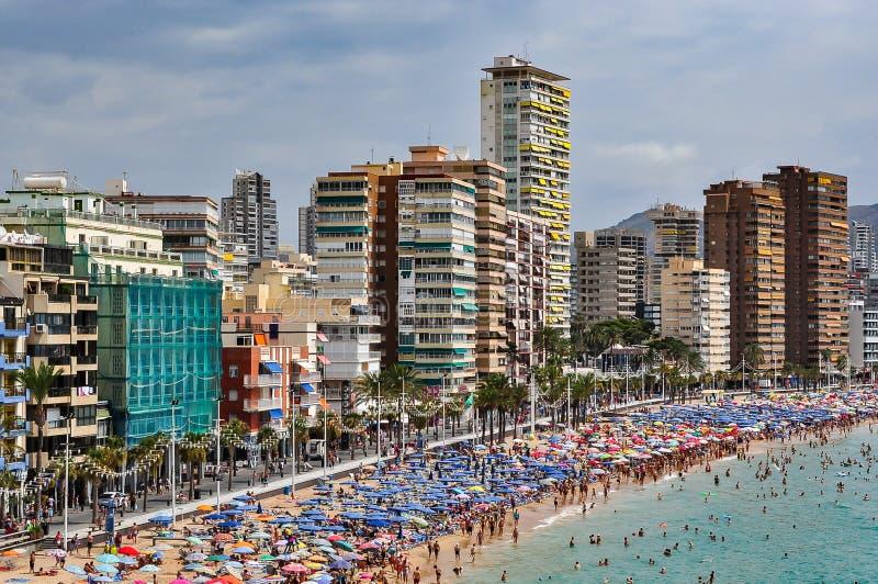 拥挤海滩贝尼多姆在一多云天 免版税库存照片