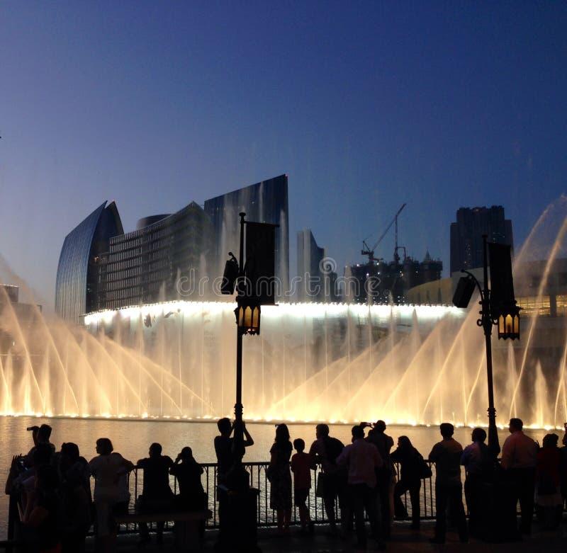 拥挤观看迪拜购物中心喷泉和光 免版税图库摄影