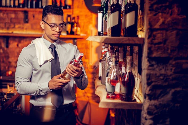 拥有酒吧的富有的商人看瓶酒精 库存照片