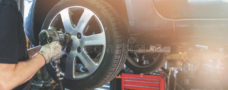 拧紧轮子的汽车修理师在汽车修理车库 免版税库存照片