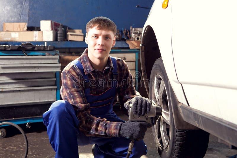 拧紧或松开被举的automobi的车轮汽车修理师 免版税库存图片