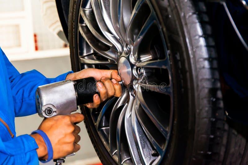 拧紧或松开车轮的技工在汽车服务车库 库存图片