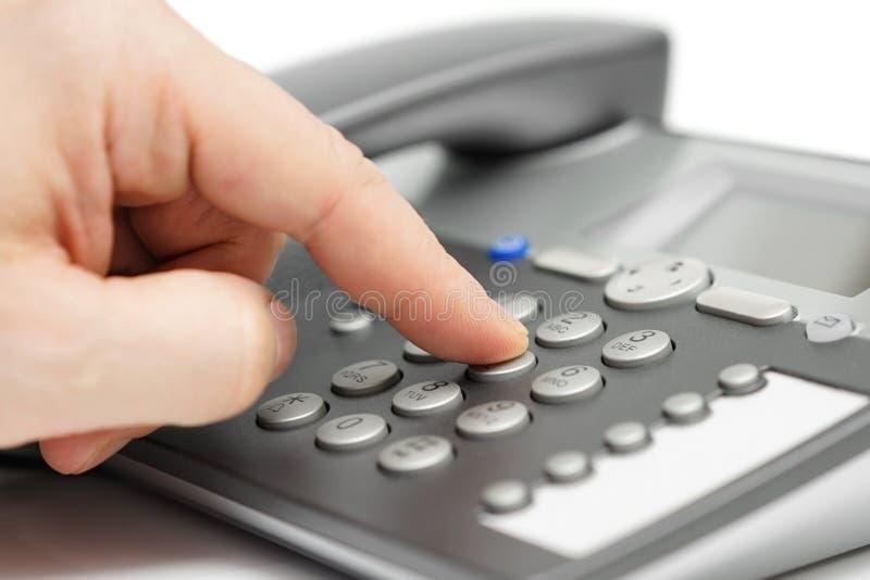 拨号在电话的手指特写镜头 用户支持概念 免版税库存图片