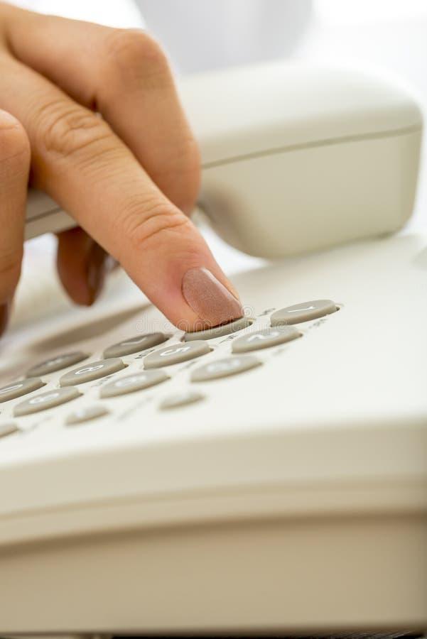 拨在白色lan的女性手特写镜头一个电话号码 库存照片