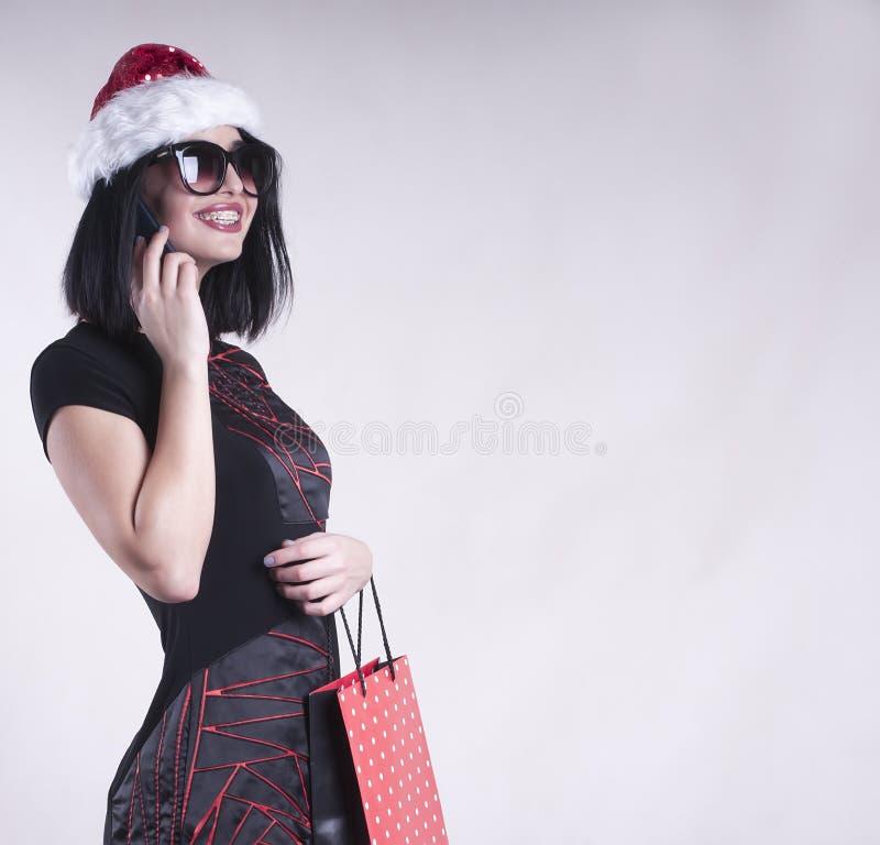 括号的美丽的女孩加盖圣诞老人,成人,假日,帽子,女性,圣诞节,年轻人,圣诞老人,盖帽,购物的智能手机的clapackage 免版税库存图片