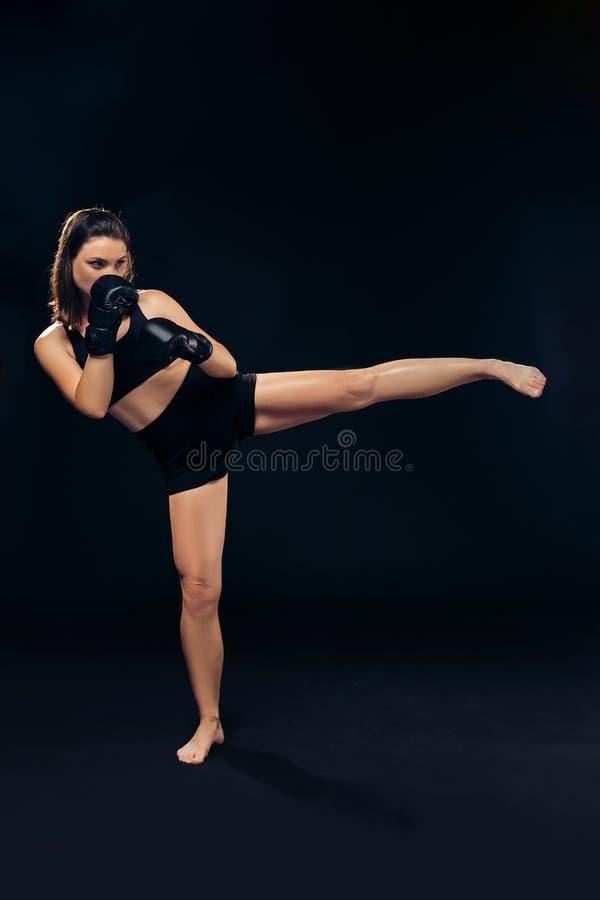 拳击手套的运动妇女在演播室实践空手道 库存图片