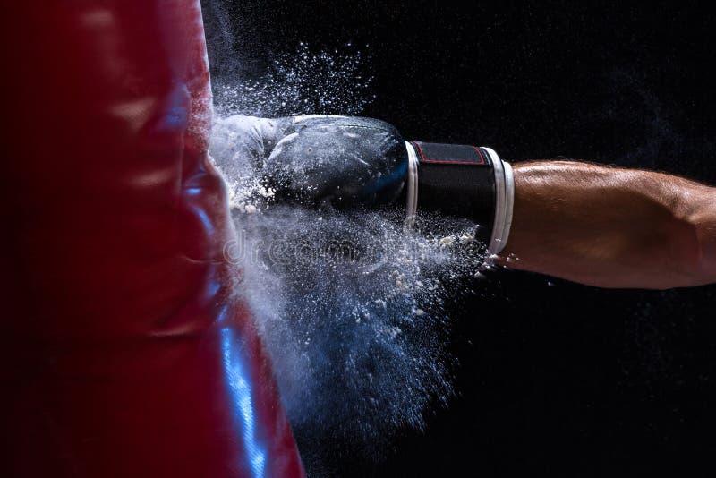 拳击手的特写镜头手在冲击的时刻对在黑背景的沙袋 库存图片