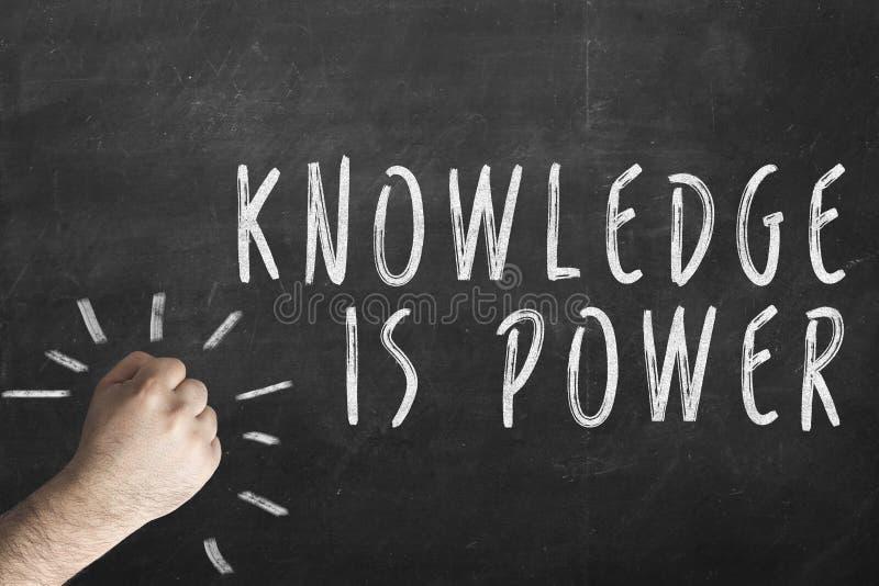 拳头和题字知识是在黑板的力量 库存图片