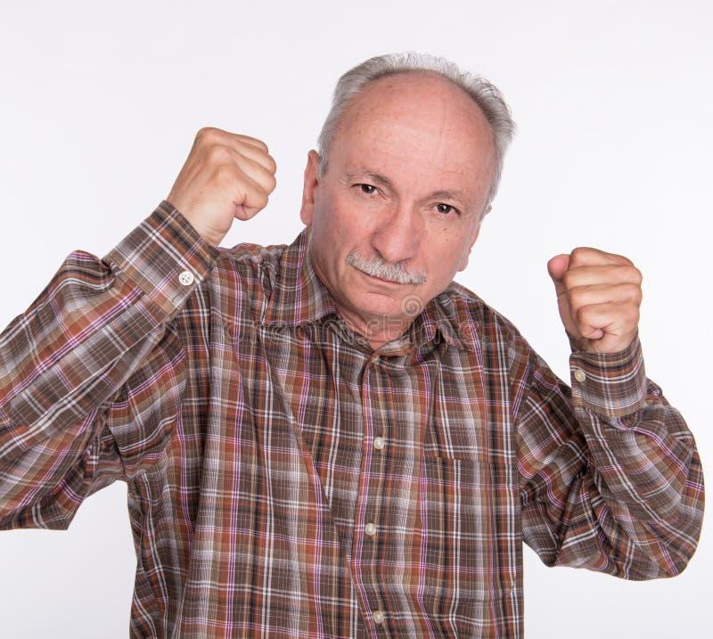 拳击手姿势的成熟人与被举的拳头 免版税库存照片