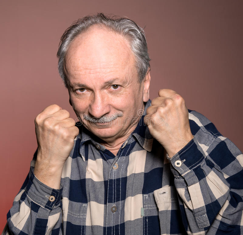 拳击手姿势的成熟人与被举的拳头 库存照片