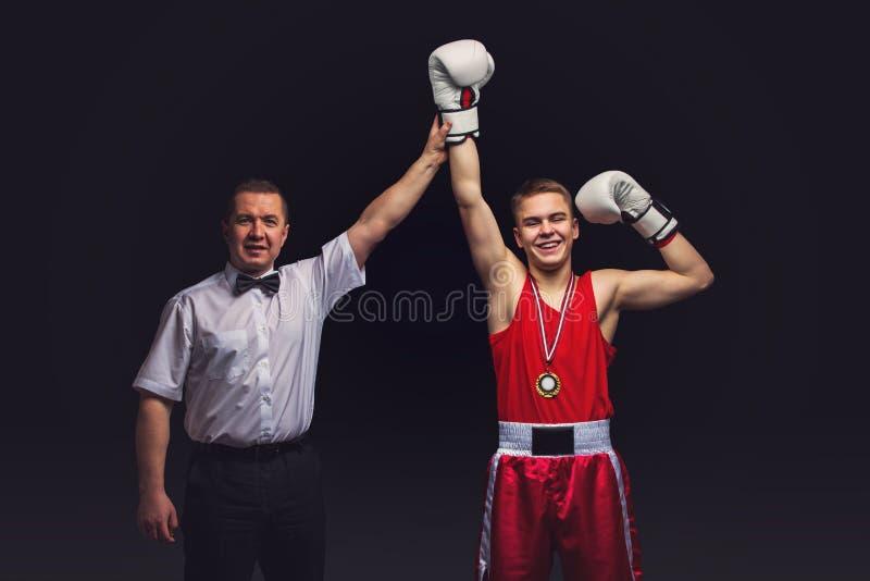 拳击裁判员给奖牌年轻拳击手 免版税库存照片