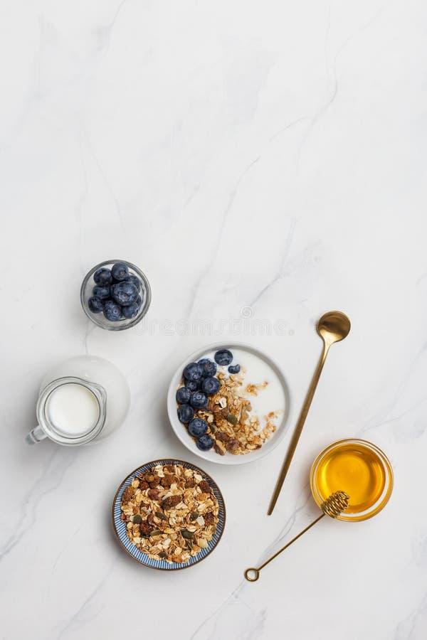 拷贝空间粥用燕麦、牛奶、蓝莓和蜂蜜在白色背景 免版税图库摄影
