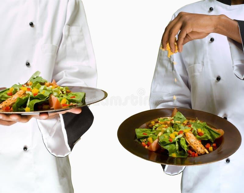 拼贴画主厨&在沙拉的sprinking的干酪 免版税库存照片