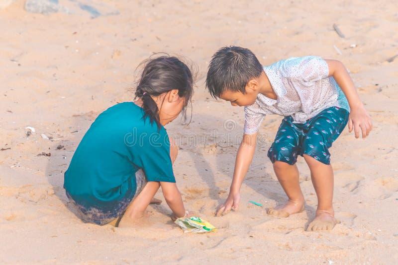 拾起他们在环境干净的概念的海滩发现的塑料瓶和gabbage的孩子 免版税图库摄影