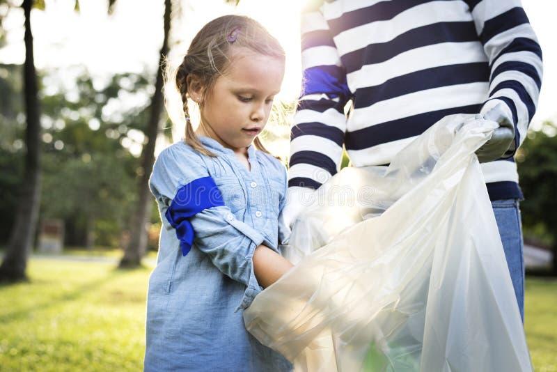 拾起垃圾的孩子在公园 免版税库存图片