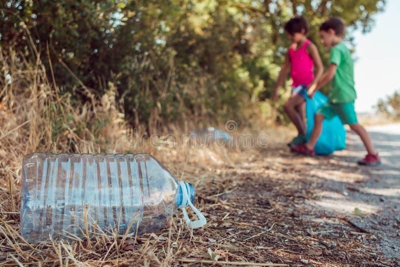 拾起垃圾的孩子在有塑料袋的森林里 志愿,慈善和生态概念 免版税图库摄影